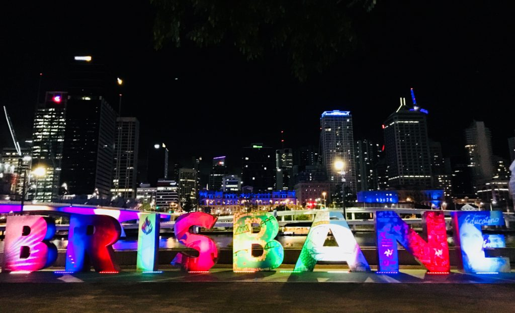 The Brisbane sign lit up at night against the cityscape