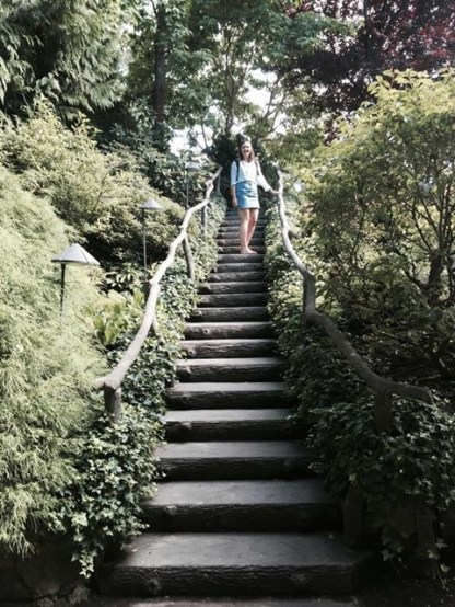 A girl standing at the top of some stairs in a park
