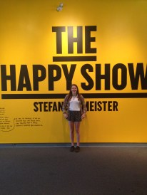 A girl standing in front of a sign saying the happy show