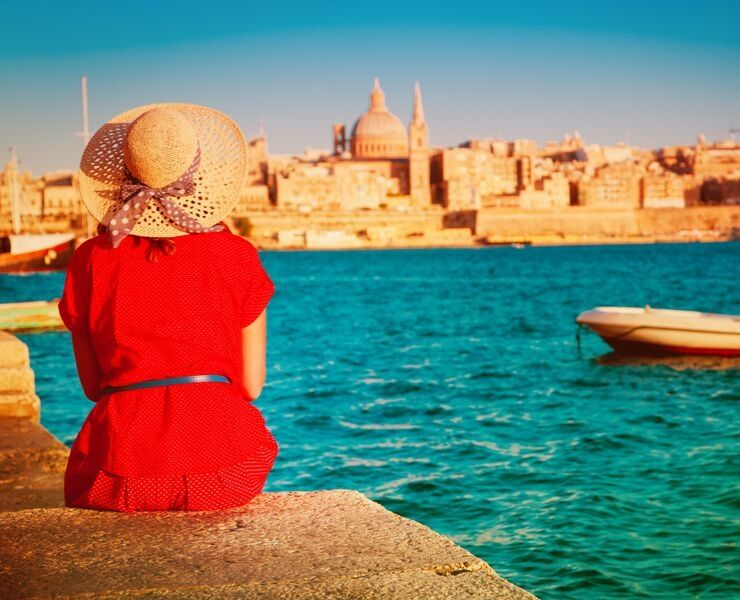 Visiting Malta - lady sitting in sun wearing a hat with Valletta in background