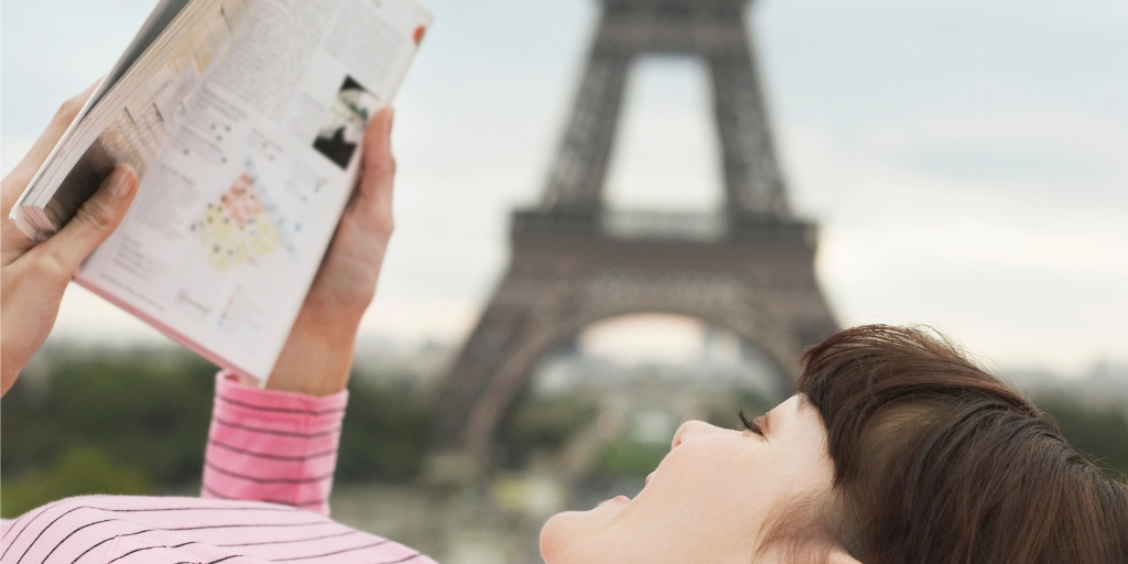 A picture of a girl with the Eiffel Tower in the background reading some of the best books about France