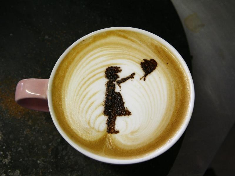 Banksy design of a girl holding a balloon in a coffee cup