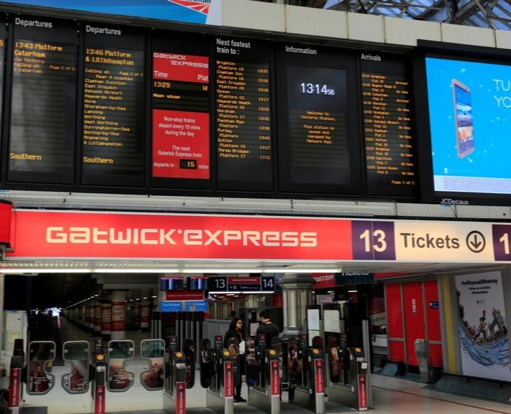UK train station showing the departure board and signs for the Gatwick Express