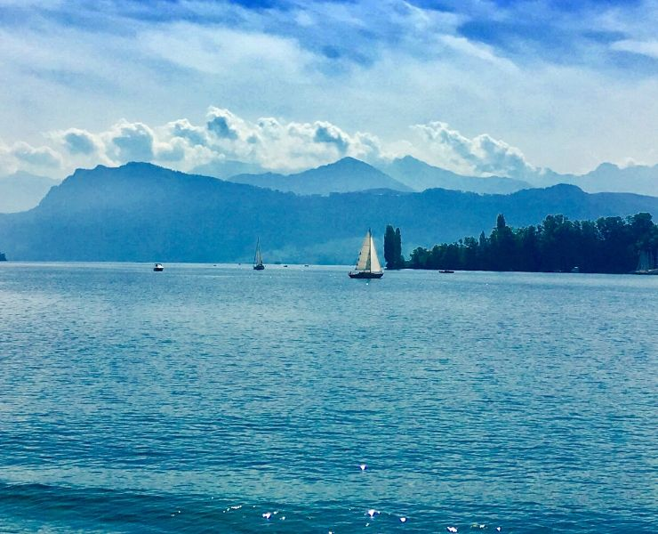 An image of Lake Lucerne with a boat and mountain featured in The Best Things to do in Lucerne Switzerland featured by top international travel blogger, Tracy's Travels in Time: take a boat trip
