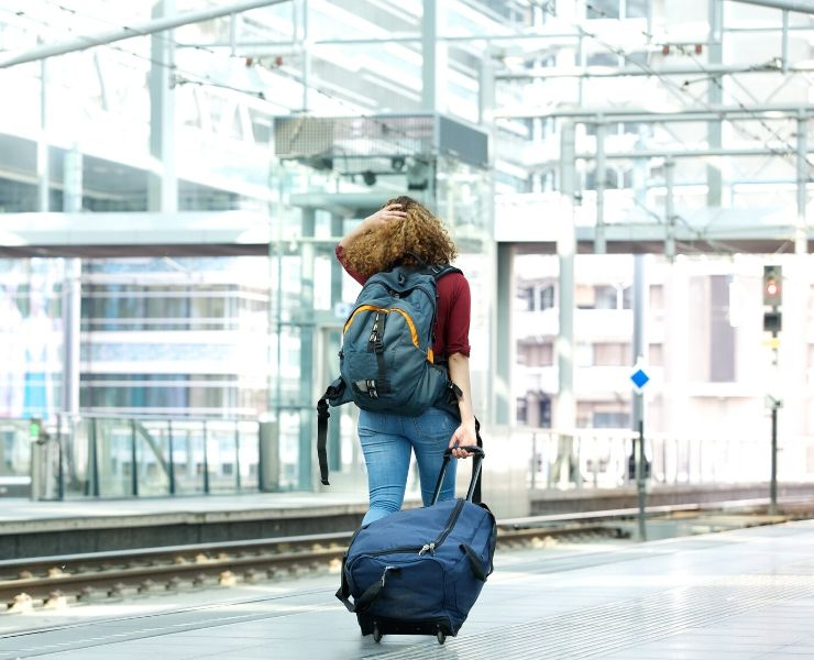 overnight train tips - girl pulling luggage along train platform
