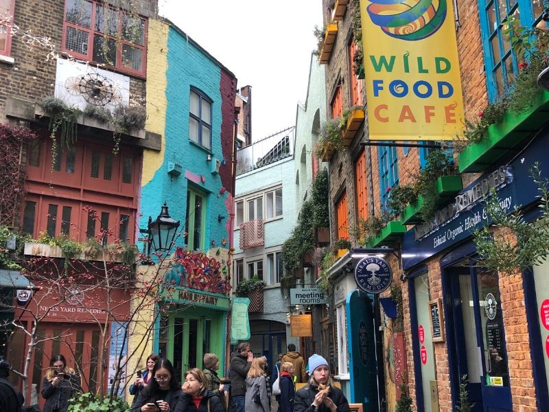 A picture showing people walking next to painted buildings in Neal's Yard London