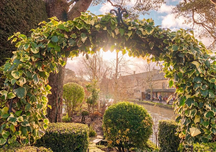 A view of Bourton on the water through an arch of shrubbery.