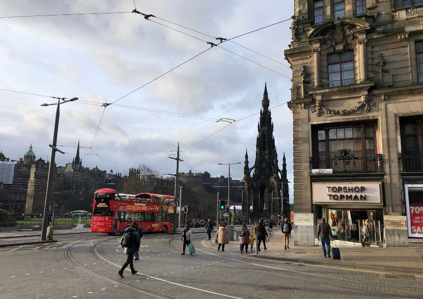 Princes Street in Edinburgh Scotland with pedestrians and a red tour bus