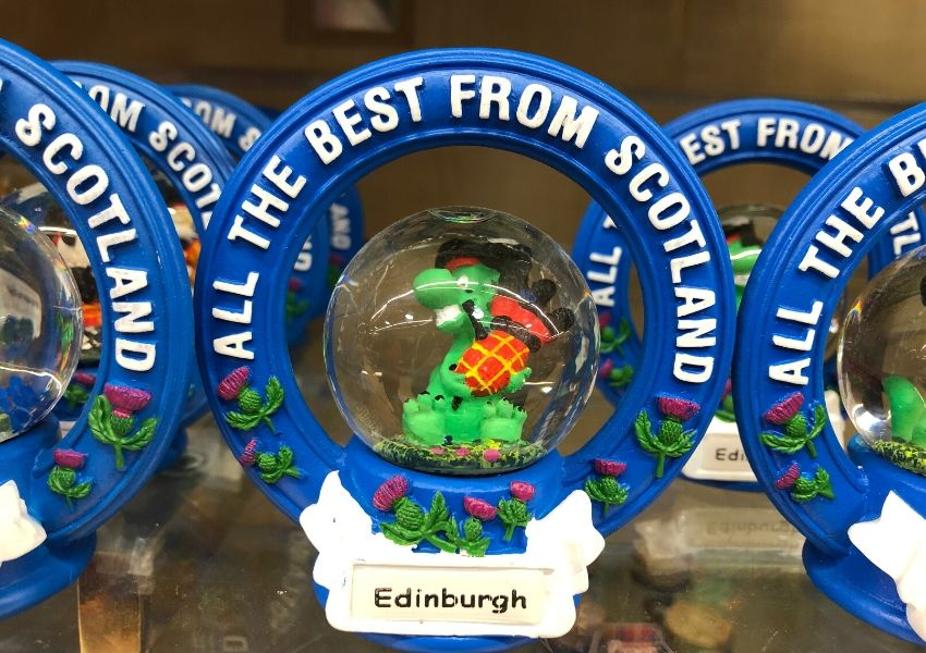 A snow globe with nessie and the words all the best from scotland