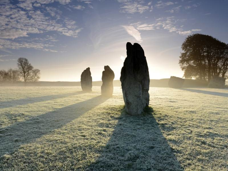 Three large stones standing in a misty field
