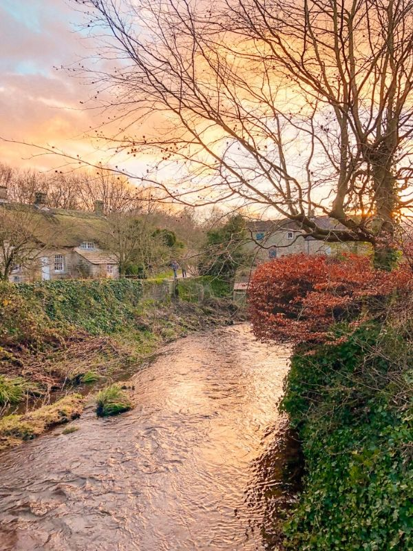 a winter scene showing a river, stone cottages and autumn colours on the bushes