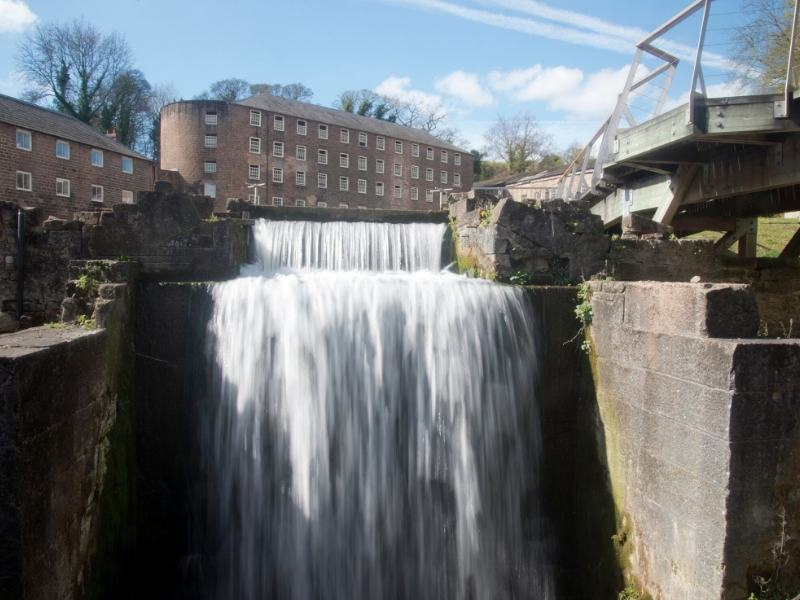 A waterfall with a mill in the background