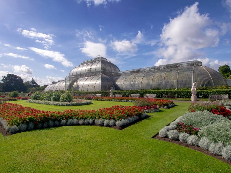 A large palm house surrounded by green lawns and red flowers