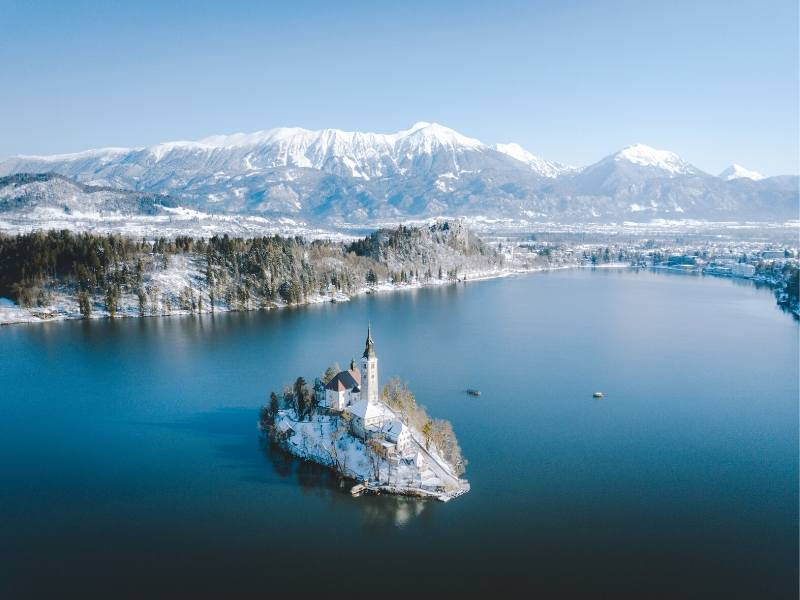 Lake Bled in winter with snow blanketing the island and mountains