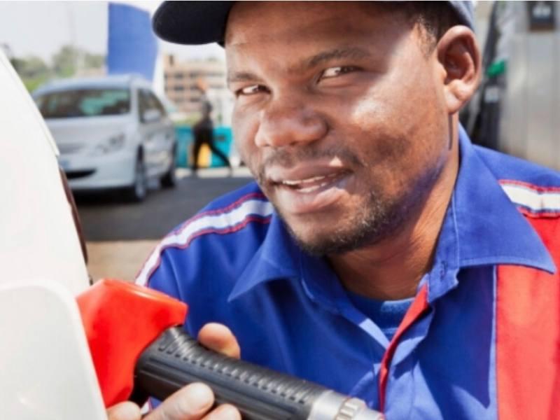 A petrol attendant putting petrol in a car