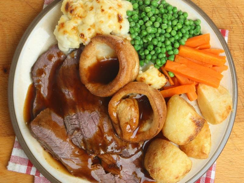 A Roast Dinner with meat, vegetables and Yorkshire Pudding on a white plate
