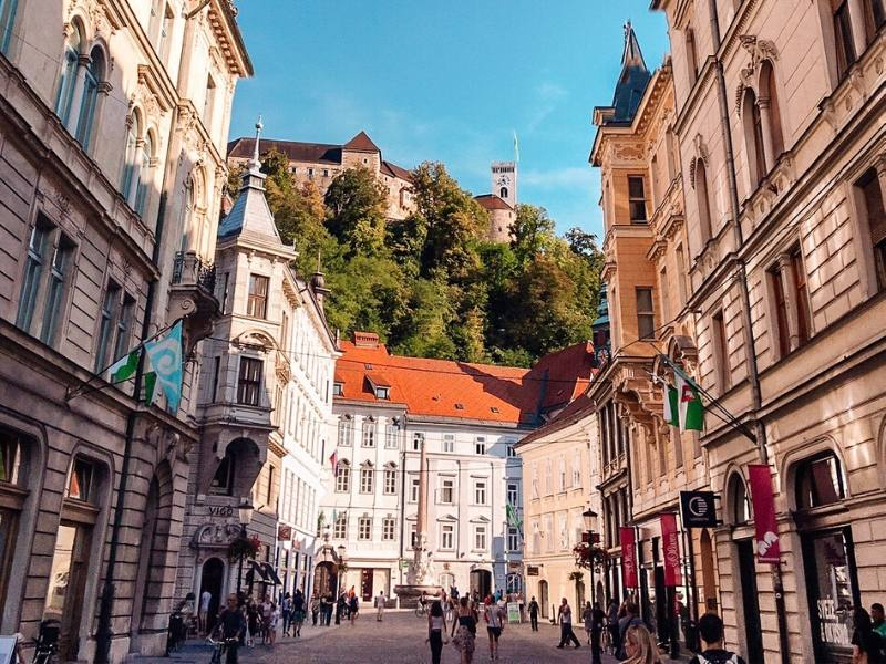 A pedestrianised street in the Old City Ljubljana with the castle in the background
