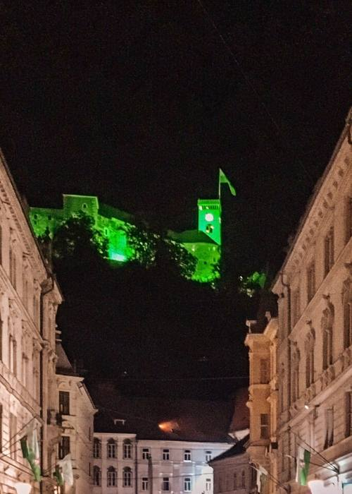 Ljubljana castle lit up at night with a green glow