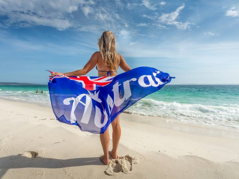 A woman standing on a beach holding an Australian flag