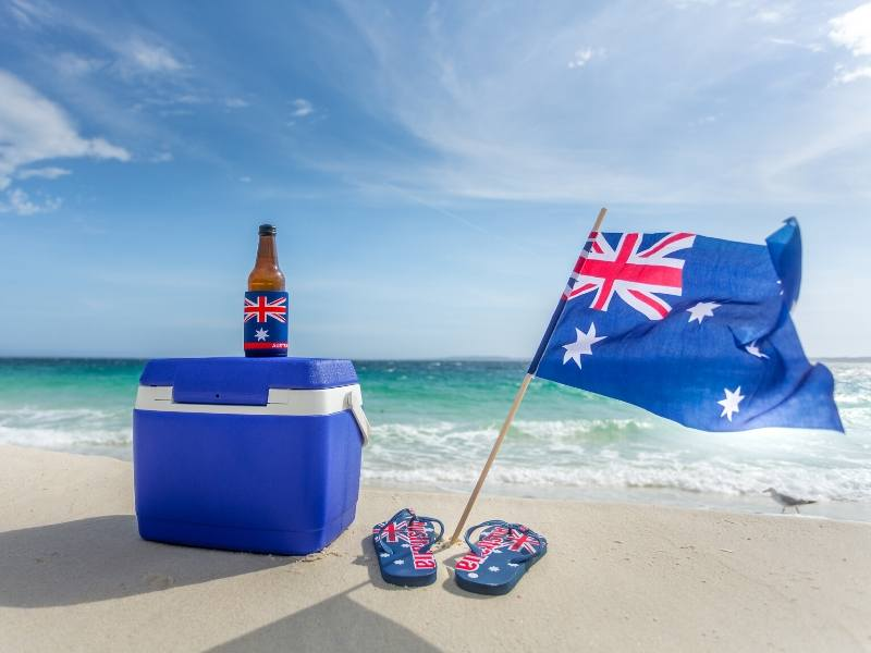 Australian flag with a pair of thongs on a beach!
