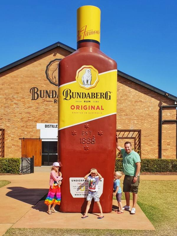 Big bottle with a family standing under it