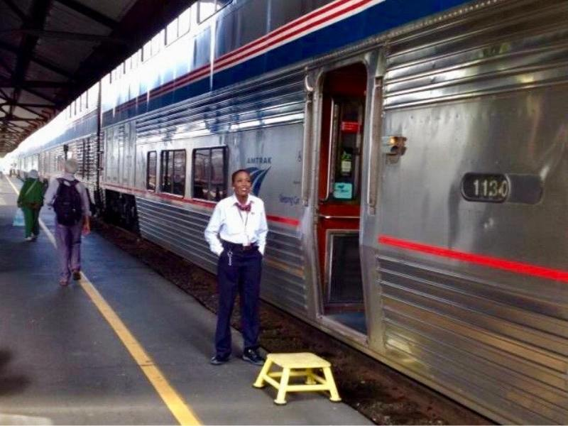 Lady standing outside the Coast Starlight train at Seattle train station.
