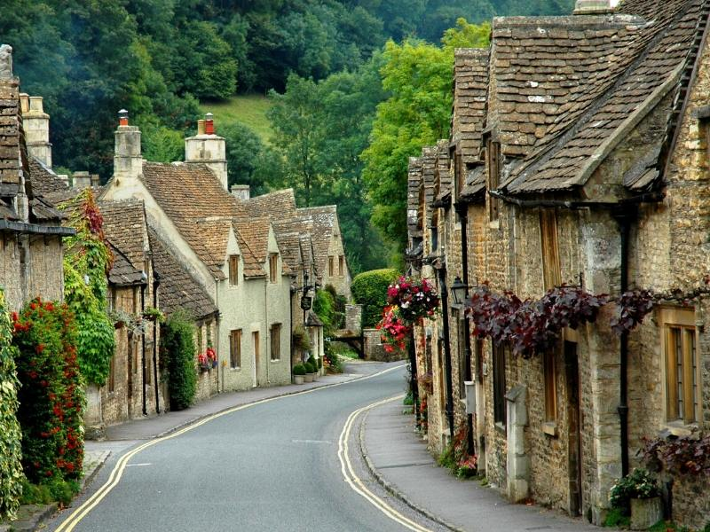 Stay in Airbnb Cotswolds Cottages as pretty as those in the image with slate roofs and flowering baskets