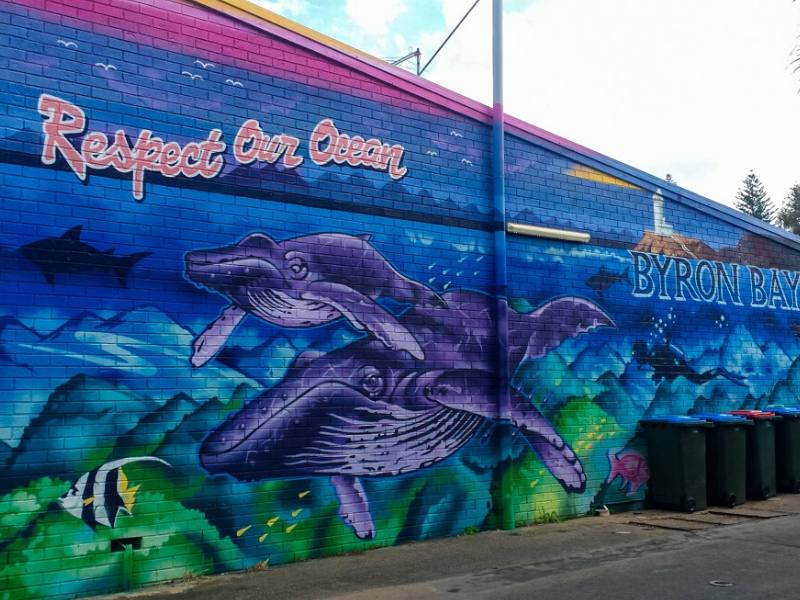 A wall mural showing 2 whales and the words respect our ocean in Byron Bay