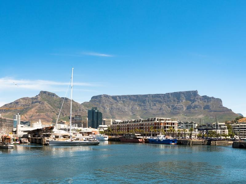 A view of Table Mountain and Cape Town's V&A waterfront with boats