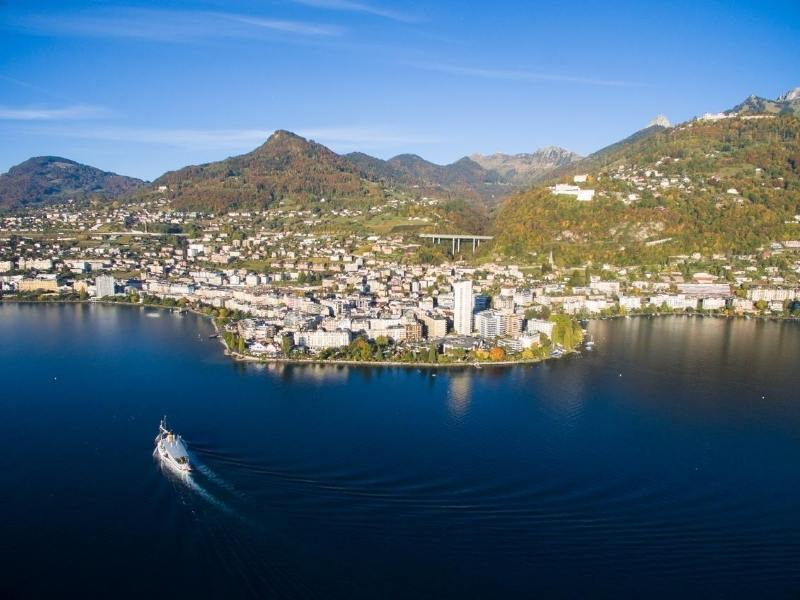 An aerial shot of Montreux on Lake Geneva with a boat crossing the lake