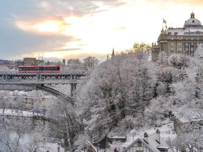 Bern in the winter snow with a red bus crossing a snow covered bridge