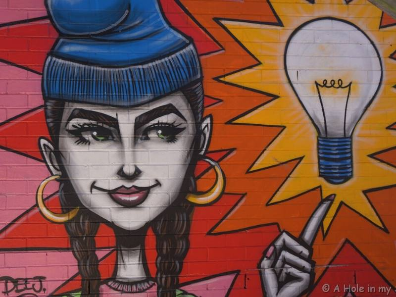 A colourful piece of street art in Perth showing a woman pointing to a light bulb