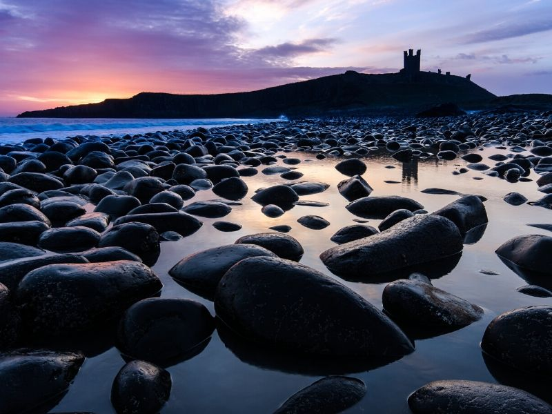 Dunstanburgh Castle in silhouette at sunset