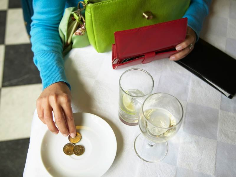 A person leaving a tip on a plate