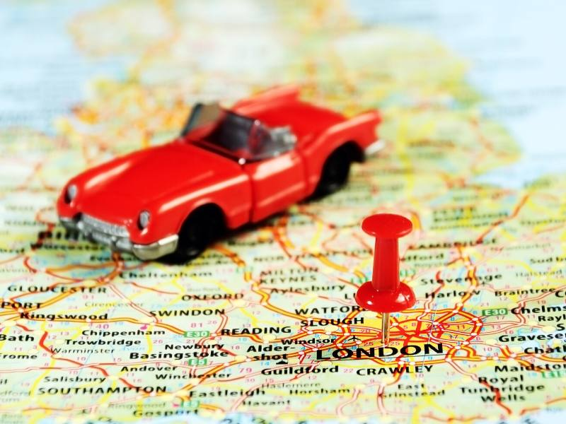 A map of London and a model red car all things about visiting england for the first time