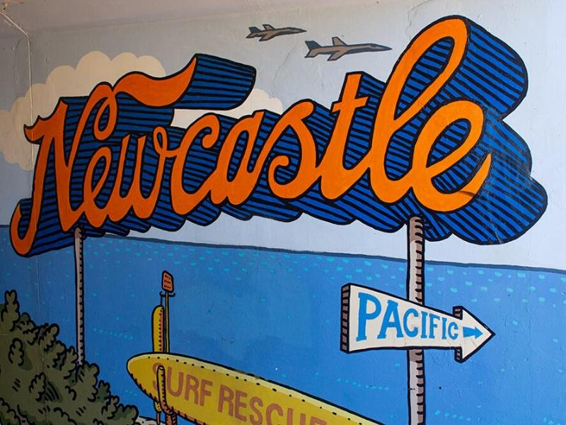 Mural of the word Newcastle with a surf board and sign for the Pacific