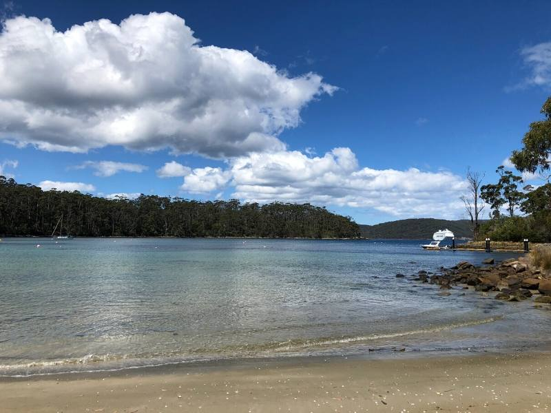 View of a boat from a beach in Tasmania