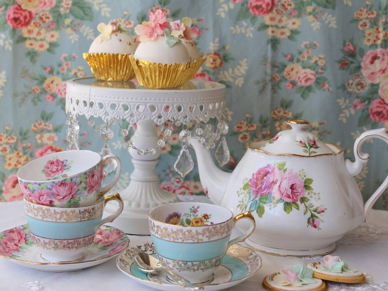 A teapot with teacups, saucers and cakes