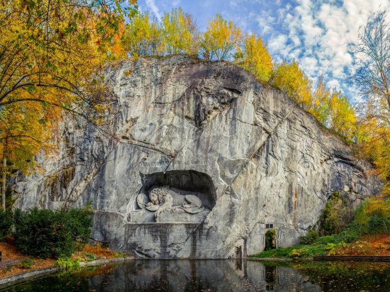 A lion carved out of the side of rock