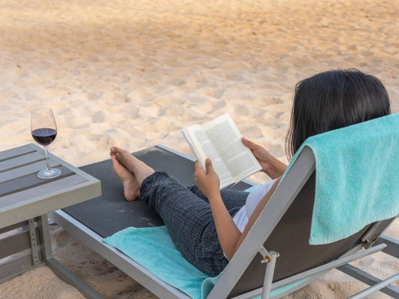 Woman sitting on a beach reading a selection of the best travel books
