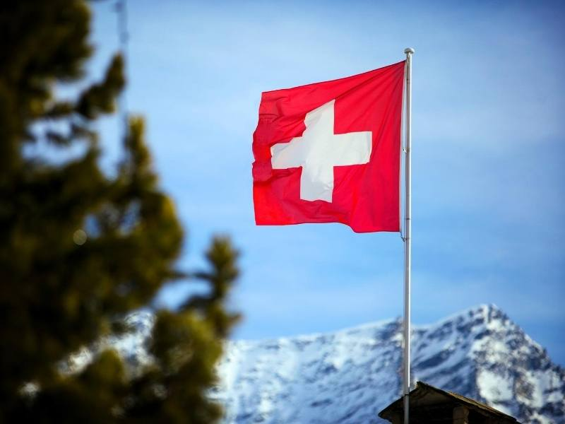 The Swiss flag with mountains in the background