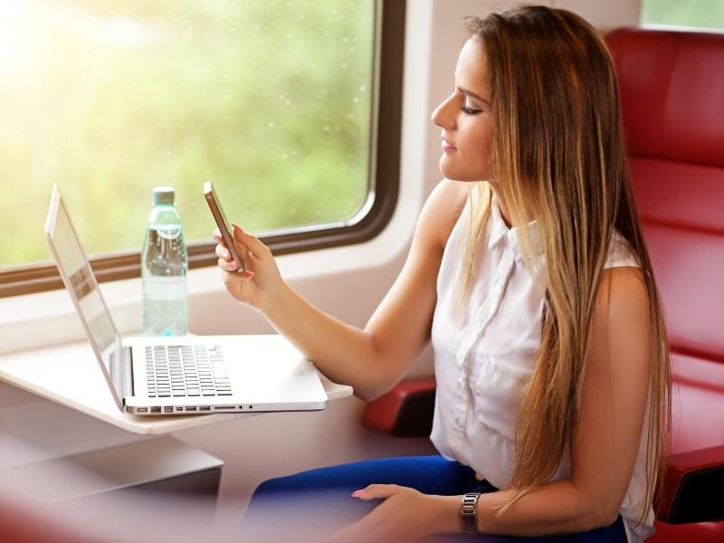 A woman using a mobile phone just one of the advantages of train travel