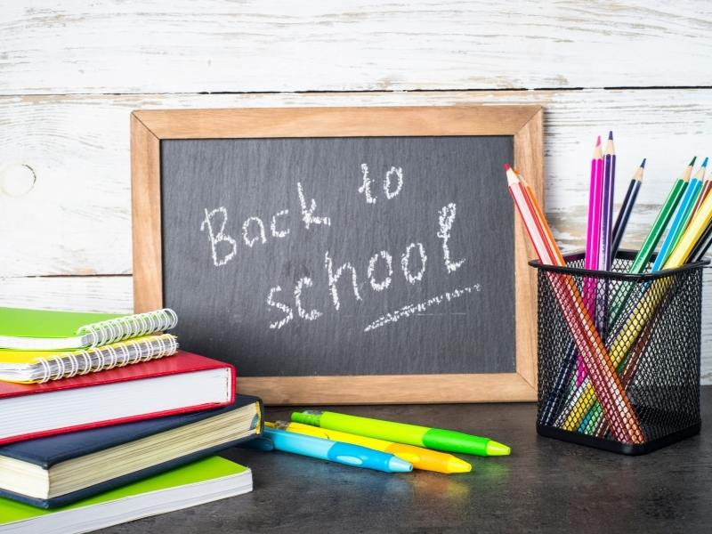 Back to school sign and lots of pens and pencils - support children emigrating by enrolling them in school quickly
