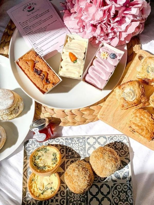 An afternoon tea in a box from Piglet's Pantry laid out on plates with a pink flower.