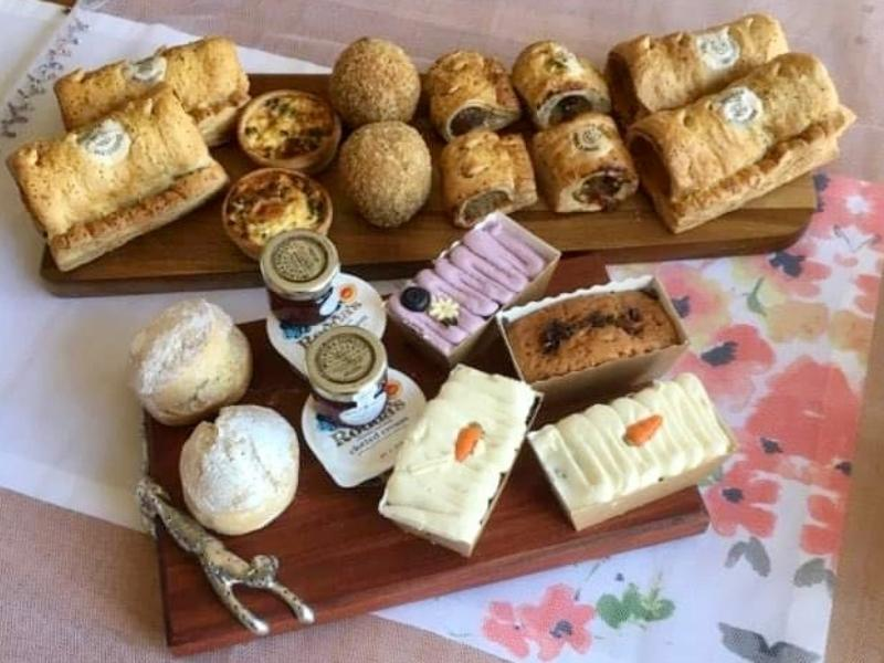 Piglet's Pantry afternoon tea in a box laid out on wooden plates.