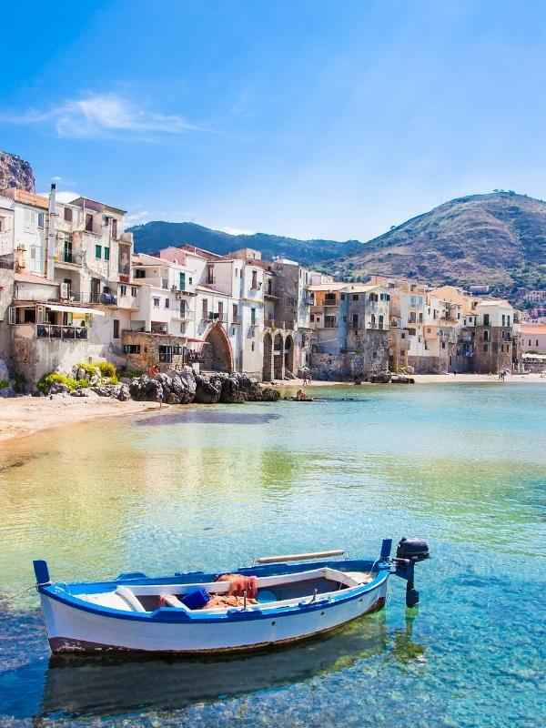 A boat on the sea near a town in Sicily as seen on some Italian TV series on Netflix