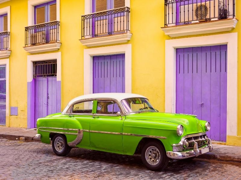 Car in Cuba in front of yellow and purple doors.