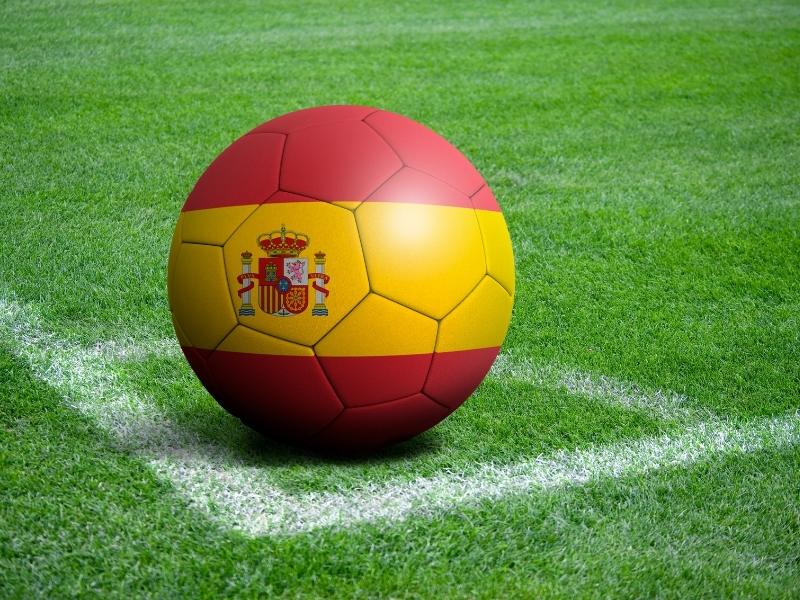 Football with Spanish flag on a pitch.
