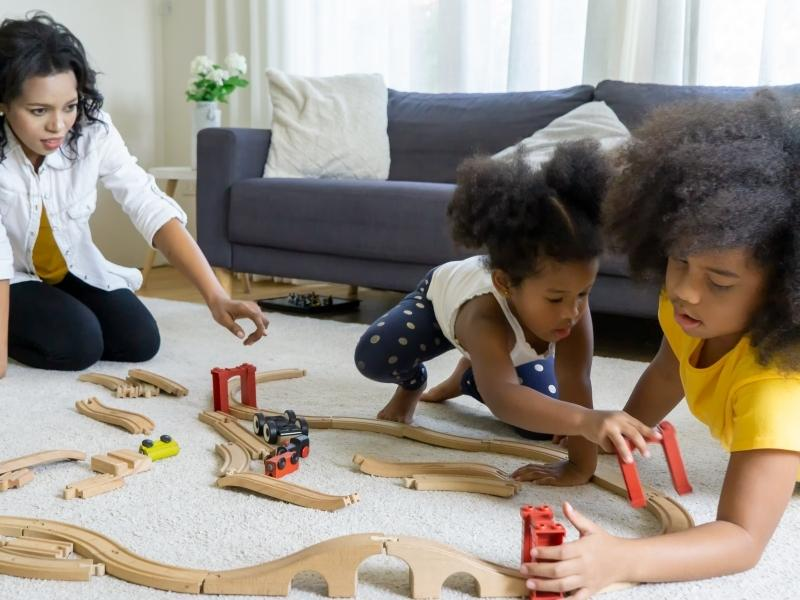 Train gifts for kids are popular at Christmas in the photo 2 children are playing with a wooden train set.