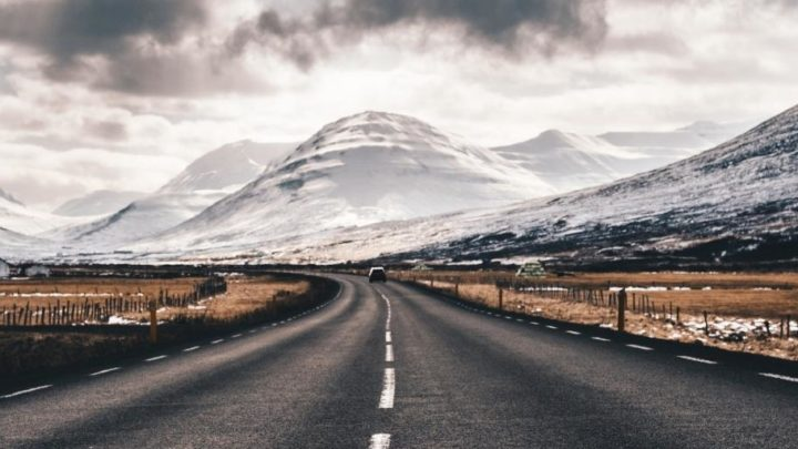 A road surrounded by snow covered mountains